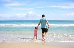 man and daughter walking on beach, rehab from home