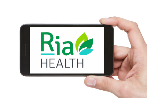 hand holding phone with the Ria Health App