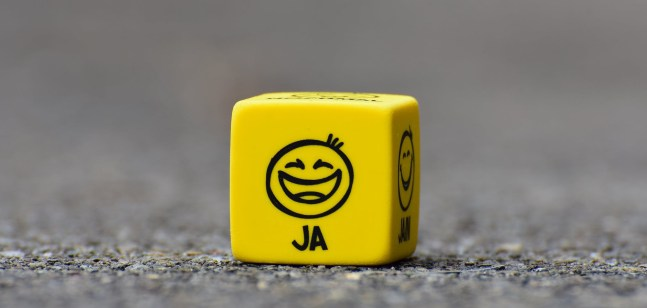 "A yellow cube thar is faced on a side that has a smiley face. under it sais ""ja""."
