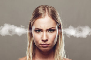 Angry looking blonde woman looking straight ahead with steam coming out of her ears.