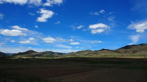 The landscape cut in half by a big puffy white cloud.