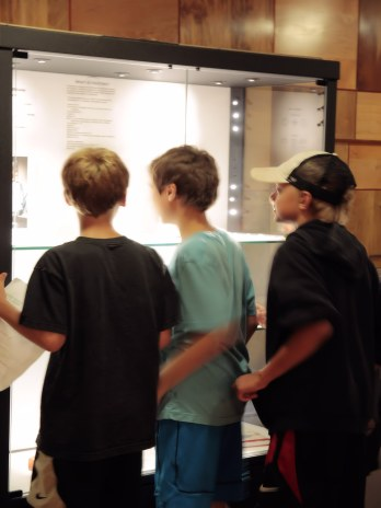 Three boys explore the meteorite exhibit in the Rice Northwest Museum.