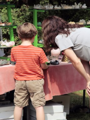 Child and woman inspect rocks in vendor booth at Summer Fest.