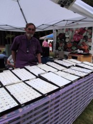 Vendor displays fine cut precious gems in booth.