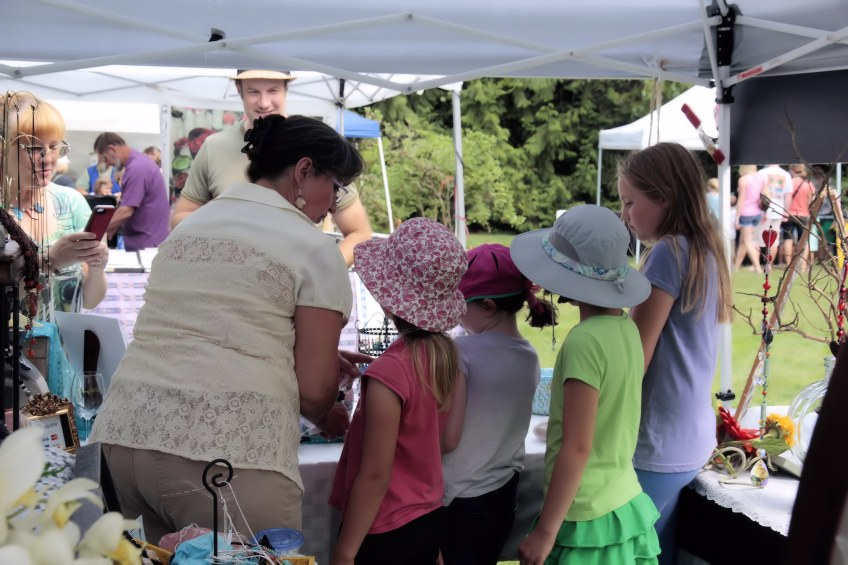 Children explore a vendor's exhibit and goods at Summer Fest.