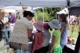 Children explore a vendor's exhibit and goods at Summer Fest.