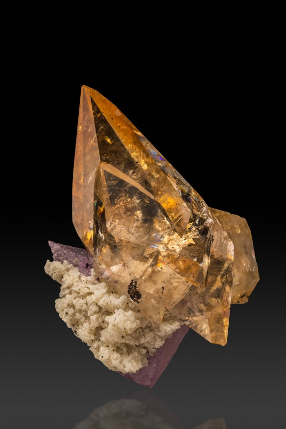 A large, clear orange calcite points to the upper left of the image. It appears to be bursting forth from a gray and purple base, barely visible on the bottom left. On a black background.
