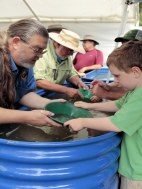 Volunteers work with children to pan for gold.