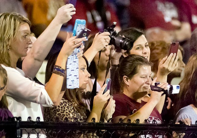 Parents and friends photograph cheerleader camp participants at a recent football game in Ada using camcorders, smart phones, tablets, and digital SLR cameras.