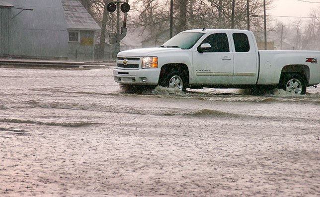 A pickup truck carefully navigates a flooded intersection in Ada this morning.