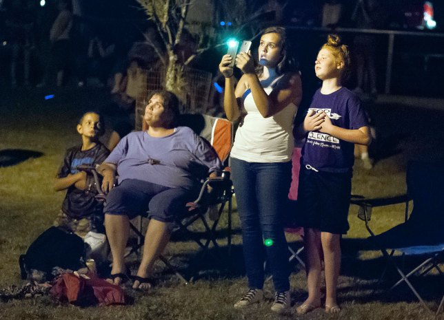 A woman uses a phone to record the fireworks display in Wintersmith Park.