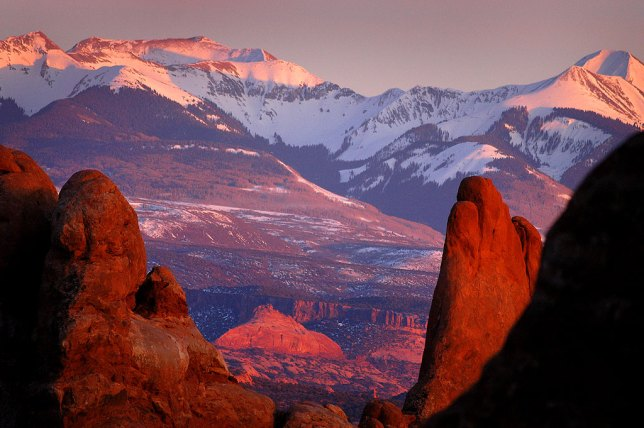 The last rays of setting sun catch snow in the La Sal Mountains with the Windows Section of Arches National Park, Utah, in the foreground, in March 2004.