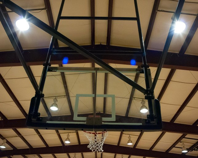 I was shooting last night at a basketball tournament with a lens with a notable tendency to exhibit ghosting, the Sigma 15-30mm f/3.5-4.5. You can see the obvious blue blobs adjacent to the ceiling lights.