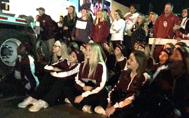 The Ada Couganns sit on Main Street and watch a skit set on a flatbed truck. The bottom of this image is in deep nighttime shadows, and full of noise.
