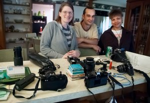 Jamie and her husband Ian, along with a friend of theirs, pose with some of their collected cameras, including the Pentax Auto 110, in 2012.