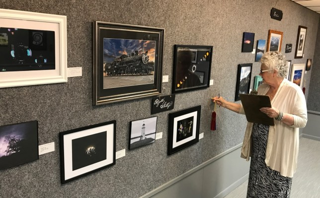 An Artists of the Arbuckles Gallery staff member prepares to place ribbons on items I selected at their spring photography show.