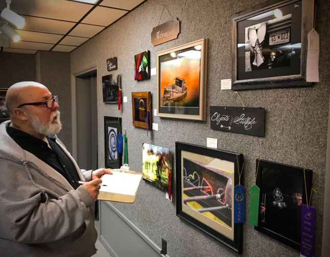 Photographer Royce Gideon makes notes about some of the image on display at the Artists of the Arbuckles Gallery Thursday.