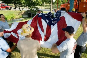 OG&E and the Ada Fire Department raise the giant flag at the entrance to Wintersmith Park