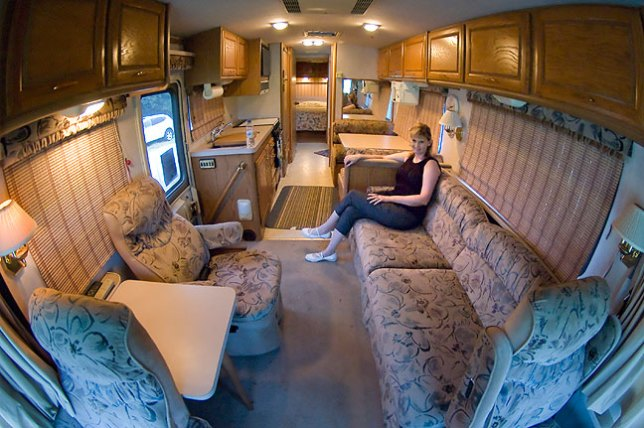 "Abby sits on the couch in the main ""living room"" area of the RV; this couch folds down to make a bed, as does the dining table; in the back is a queen-size bed."