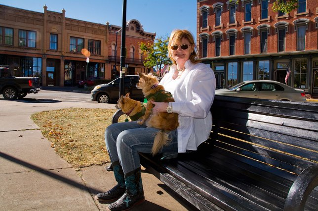 """Abby sits on a park bench in Las Vegas, New Mexico's historic Old Town Plaza, location of filming of one of her favorite television shows, """"Longmire."""" Over her right shoulder is the building that acts as the Absaroka County, Wyoming Sheriff's Office. The door still bears the logo from the show set in Durant, Wyoming, but filmed entirely in New Mexico."""