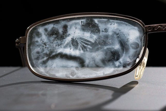 A reading glasses lens shows a collection of schmeer from the cool mist humidifier.