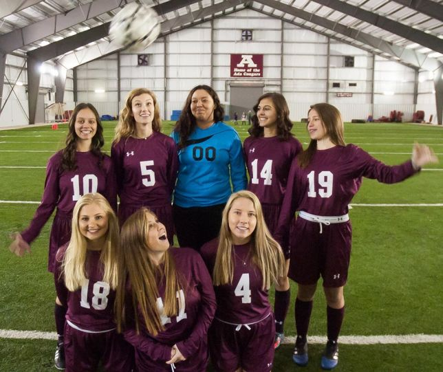 Sadie Criswell, far right, tosses a soccer ball over her fellow senior soccer players at media day today.
