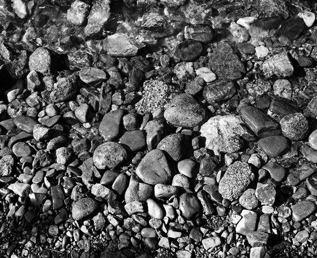 Pebbles catch boring light as the clear waters of the Pecos River flow over them.
