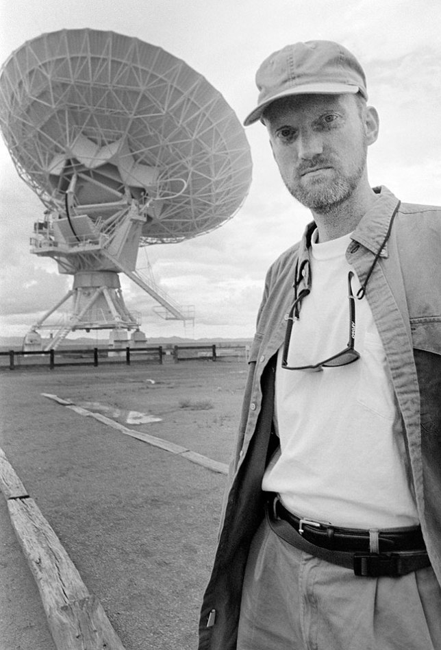 The author poses in flat, featureless light at the Very Large Array near Magdalena, New Mexico. The dreary light and the position of the radio telescope dishes resulted in shooting very few photos.