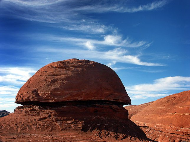 A mushroom-sharped rocks is set against a deep blue sky on the trail Canyonlands.