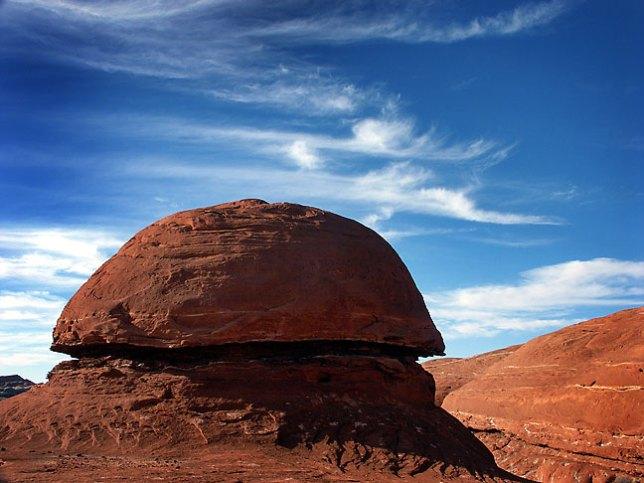 A mushroom-sharped rocks is set against a deep blue sky on the trail Canyonlands.