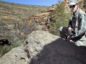 The author poses at the top of a short hike up a cliff above Sitting Bull Falls.