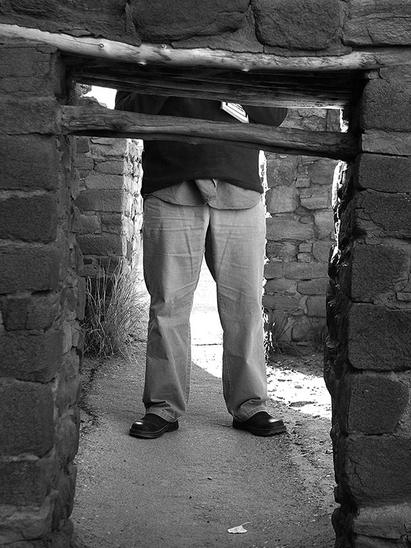 David's legs appear in doorways as her walks through Aztec Ruins National Monument.
