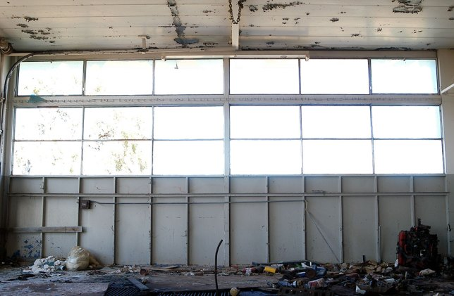 "Light fills the windows of a garage door at the abandoned service station at the ""Plague Town."""