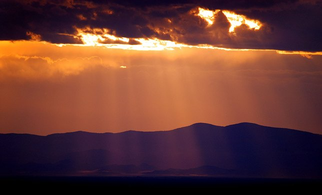 Crepuscular rays form as the sun ducks behind clouds as evening approaches in the San Luiz Valley of southern Colorado.