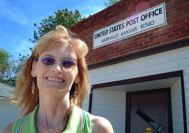 Abby smiles as she poses in Abbyville, Kansas.