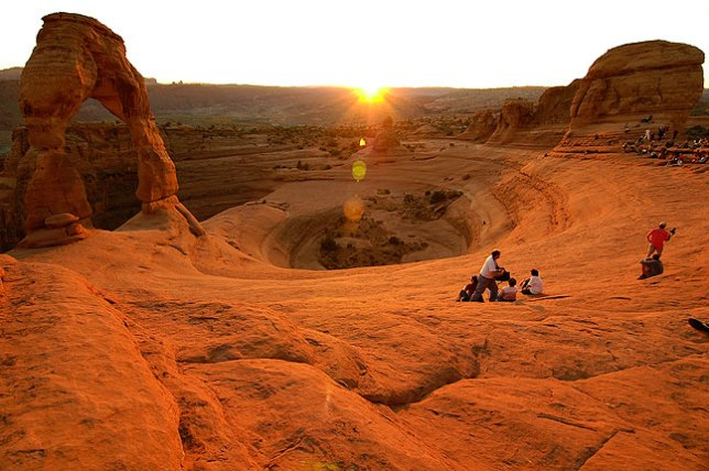 The sun touches the horizon at Delicate Arch.