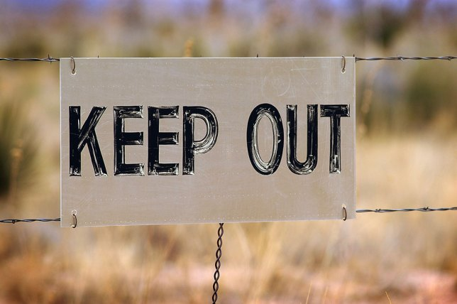 "A very well-worn ""keep out"" sign hangs on a fence at the Trinity site."