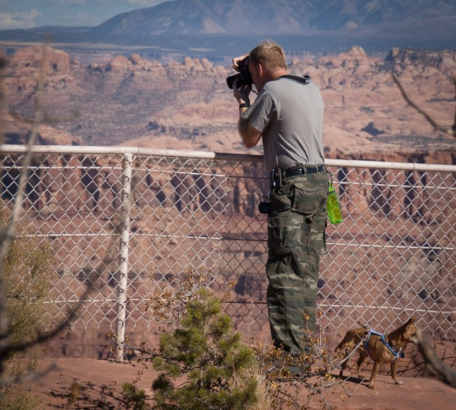 The author photographs the Anticline Overlook on Hatch Point, Utah, with Max the Chihuahua tethered to his belt.