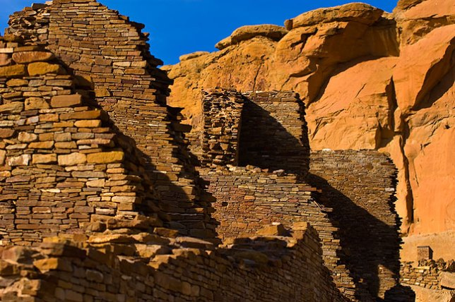This is an exterior view of the Pueblo Bonito great house in warm afternoon light.