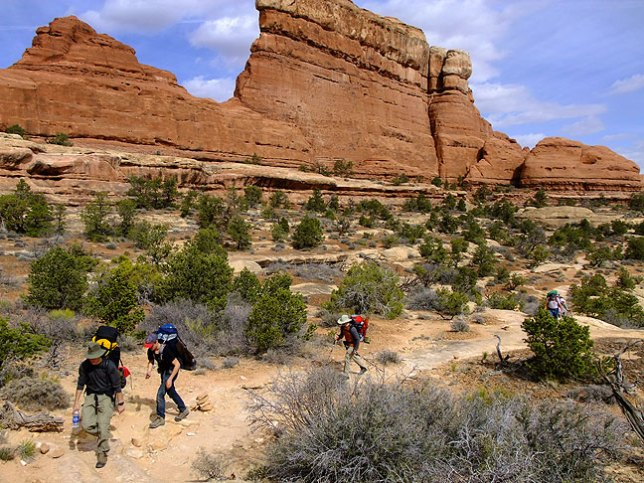 "Backpackers pass ""The Wall"" on the Chesler Park trail at Canyonlands National Park, Utah."