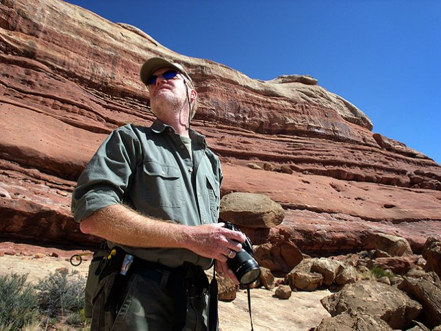 The author looks over a stone wall along the Peek-a-Boo trail.