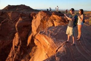 Visitors photograph Horseshoe Bend at sunset.