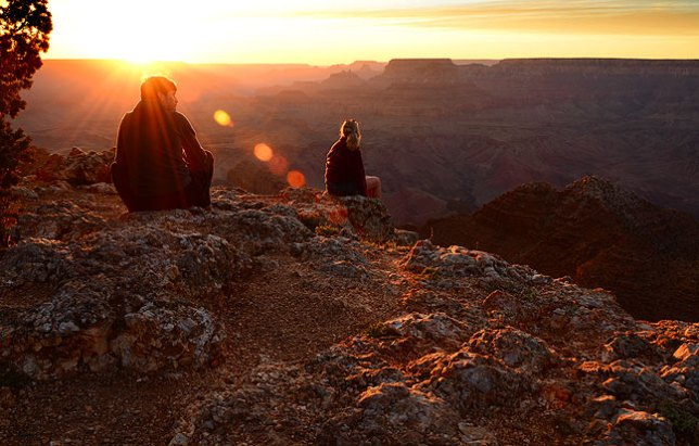 Fellow visitors take in the majesty of the Grand Canyon's Navajo Overlook at sunset.