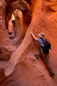 Chris from Logan, Utah, climbs a ledge in Peek-a-Boo Slot Canyon.
