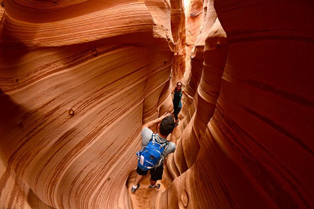 A young couple makes images in Zebra Slot Canyon.