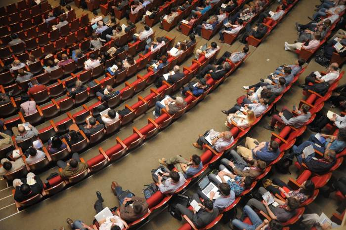 an auditorium with people watching a conference