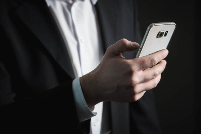 a man in a suit holding a smartphone