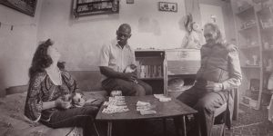 three people playing cards in a hotel room