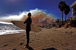 Fourteen-year-old Luke Schroder turns back to look at the smoke filled sky after surfing while fire burns in Malibu Sunday October 21, 2007.