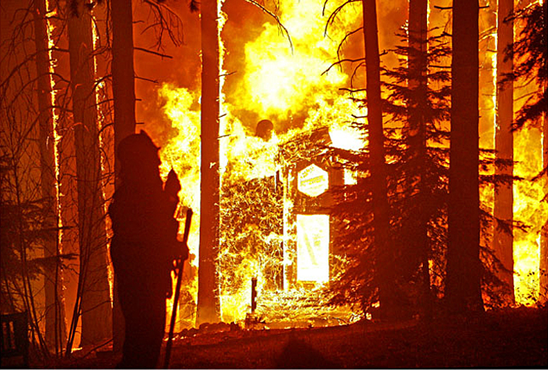 A house burns as a firefighter uses his two-way radio along Circle View Drive as wildfires burn in Running Springs near Lake Arrowhead early (2:00 am) Tuesday morning October 23, 2007.